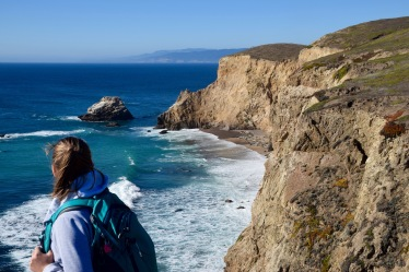 Girl hiking on the edge of a sea cliff in Point Reyes California