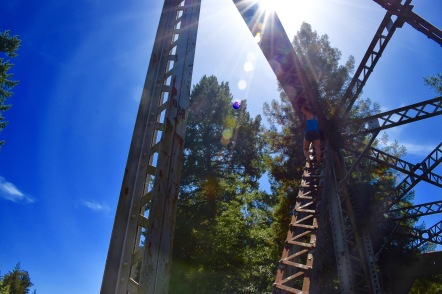 Girl climbing up the side of an abandoned railroad bridge on a sunny day