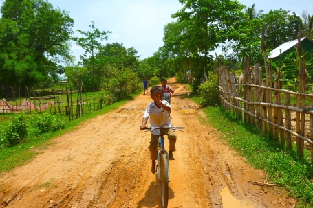 Happy Young Cambodian Boy Riding his Bike on a Dirt Road