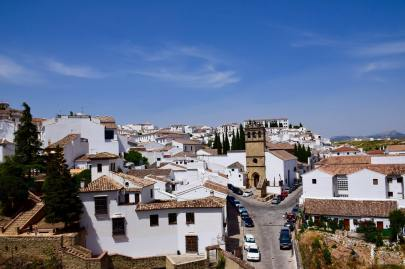 Street view of white houses and cars lining the hillside in Ronda Spain