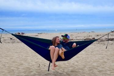 Couple enjoying their blue Eno hammock together on the beach in Santa Cruz