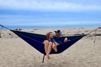 Couple enjoying their blue Eno hammock together on the beach in Santa Cruz