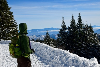 Taking a break from cross country skiing to enjoy the view of neighboring snow covered mountains