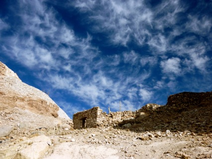 Whispy clouds about a rock structure in the Atacama Desert