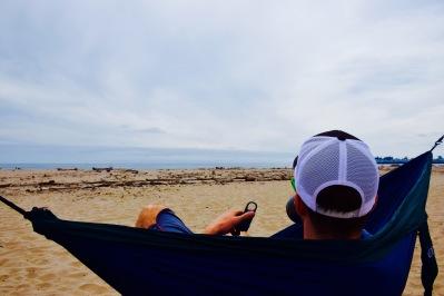 Man sitting in an Eno hammock on the beach
