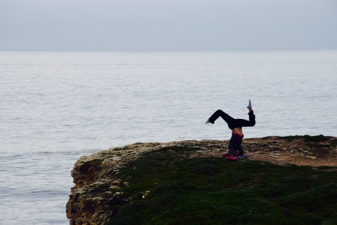 Enjoying life upside down with a headstand on a sea cliff