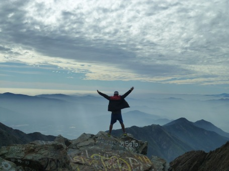 Man with his arms in the air feeling triumphant after a long, steep hike to the top of La Campana in Chile