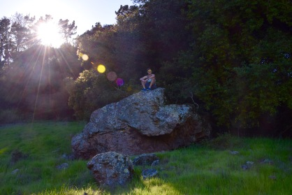 Guy sitting atop a rock outcropping