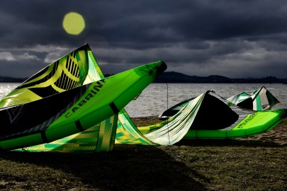 Green kite surfing kite resting on the sand