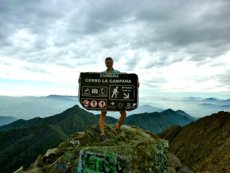 Girl holding a summit sign after making it to the top of La Campana, a mountain in Chile