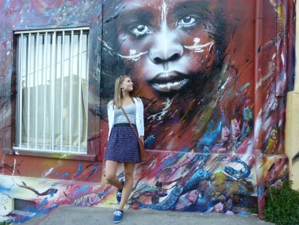 Girl standing next to a colorful mural in the UNESCO world Heritage site of Valparaiso