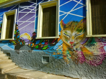 Colorful mural painting of a cat and cityscape in the UNESCO world Heritage site of Valparaiso