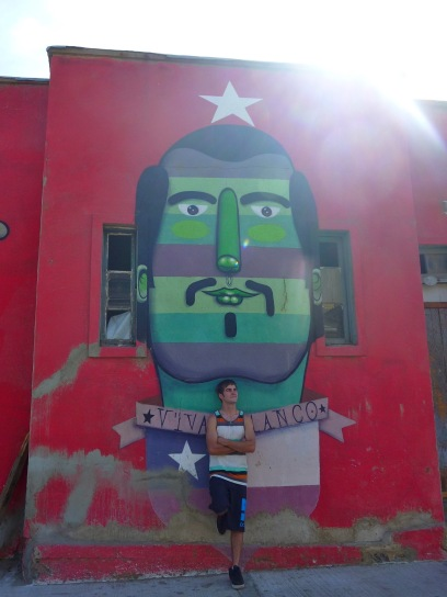 Man standing next to a mural on Cerro Polanco in Valparaiso Chile