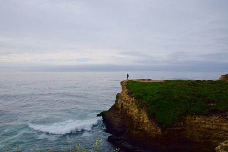 Standing on the edge of the world on a sea cliff above the ocean
