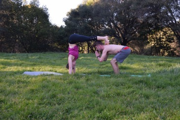 Active couple practicing partner yoga together in a grassy field