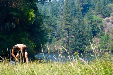 Man preparing a picnic in a grassy field next to a lake in the outskirts of Ashland Oregon