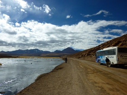 Tourist buss by a riverbed on a sunny day in the Atacama Desert in Chile