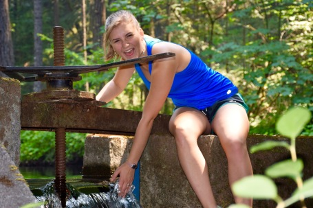 Alli laughing on the edge of a small dam in the forests of Ashland Oregon