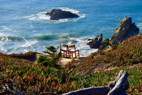 Two chairs on a cliff overlooking the ocean