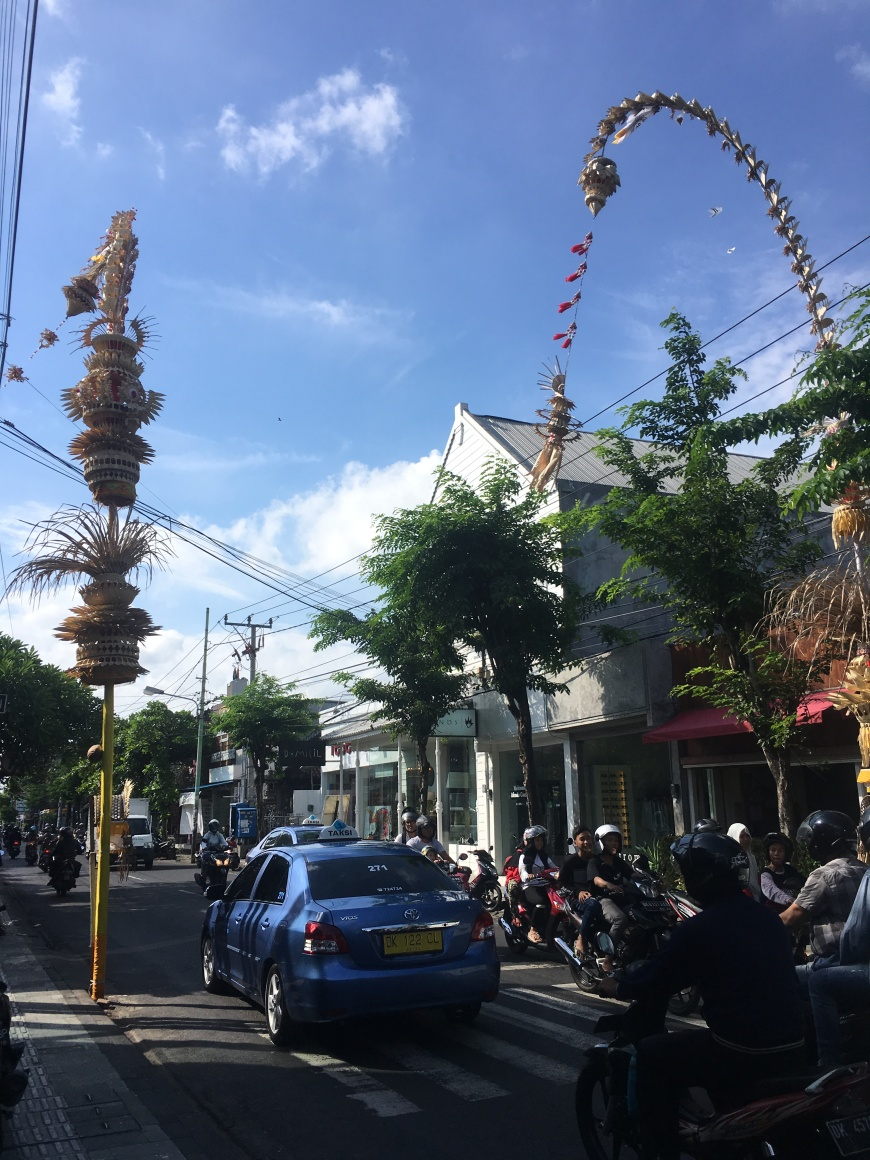 Street in Bali covered with scooters (mopeds) and a taxi