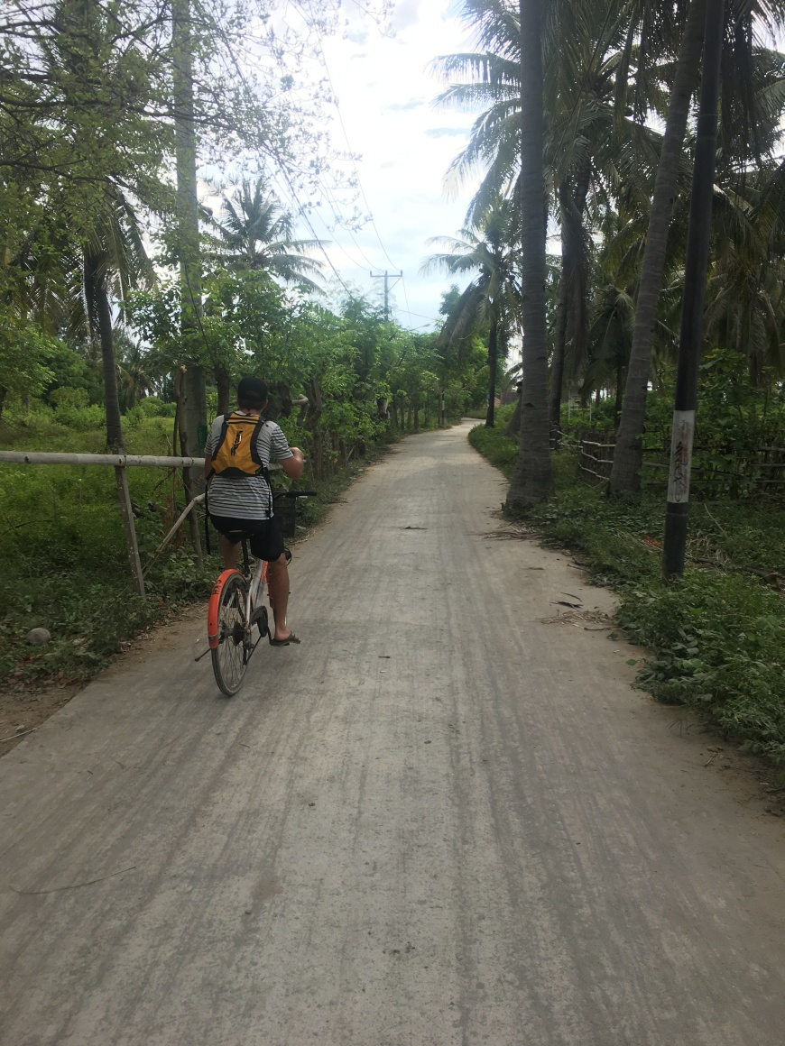 TJ biking into town from our hostel on Gili T