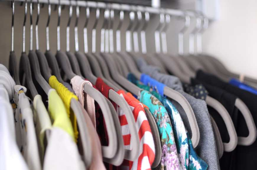 A woman's organized closet with lots of tops to choose from