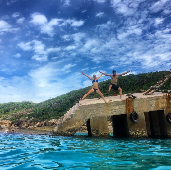 Alli and TJ jumping off the broken dock at the bottom of the windmill staircase and enjoying the blue lagoon