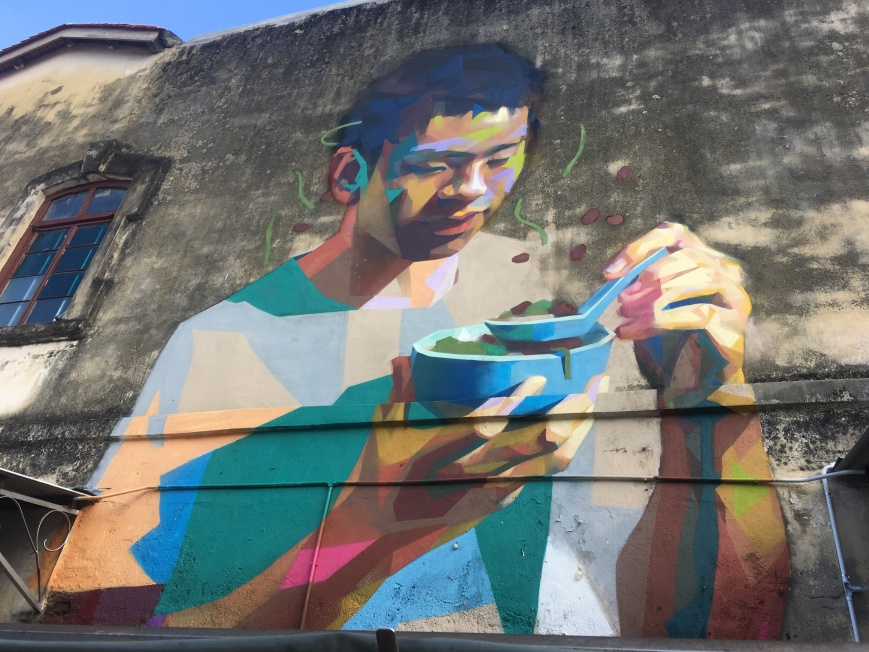 Mural of a man eating chendul outside the street stall