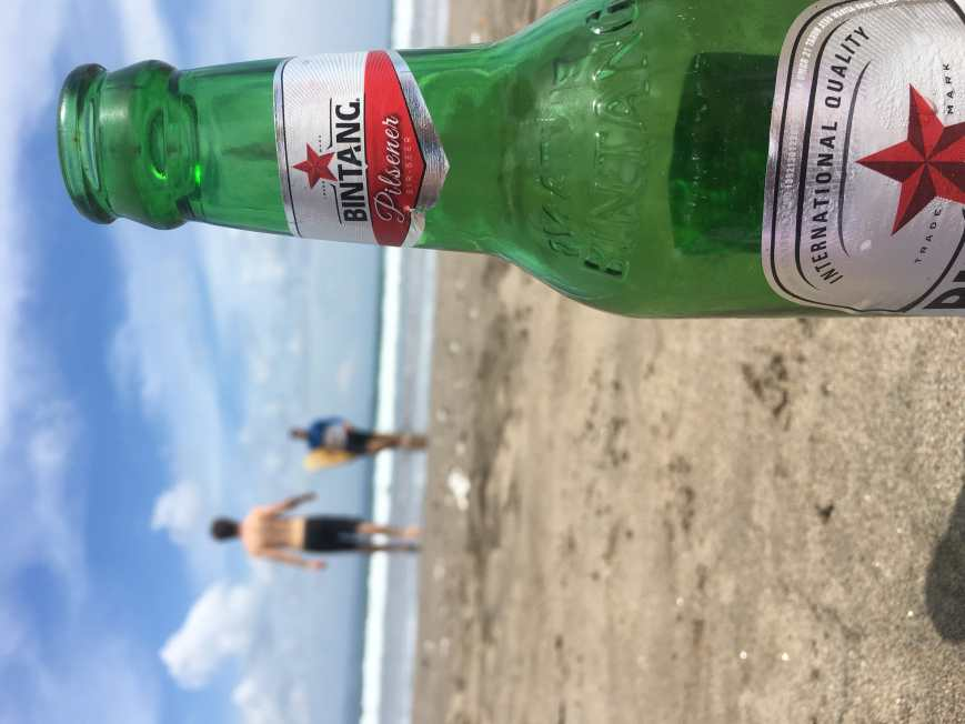 Enjoying a local Bintang on the beach in Seminyak, Bali, Indonesia with friends after a day of surfing