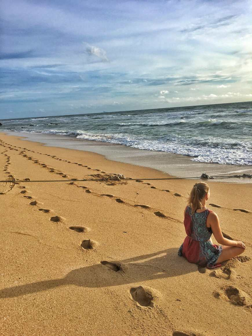Sitting and meditation on the beach at sunset in Koh Lanta Thailand with foot prints in the sand