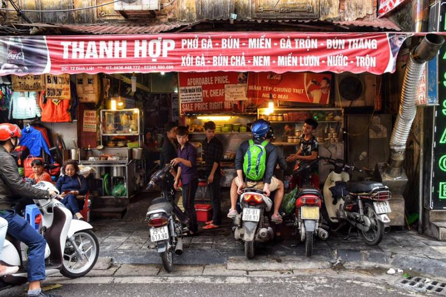 Busy resaurant with motorbikes outside in the old quarter of Hanoi, Vietnam