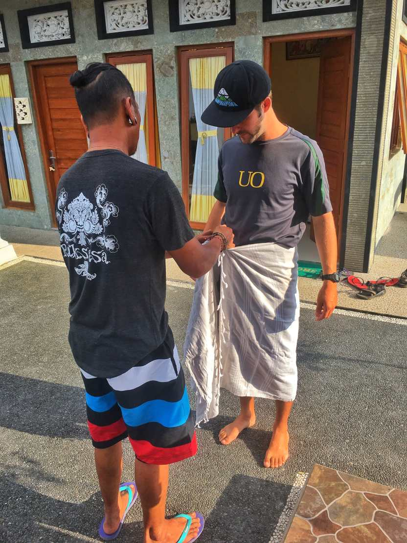 Remy teaching TJ how to tie his sarong in the traditional Balinese way before we going to Tirta Empul