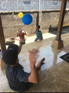 """TJ playing a game of """"keep the balloon in the air"""" with two of the family's children"""