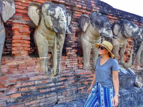 Making friends with stone temple elephants in the ancient capital of Sukothai, Thailand