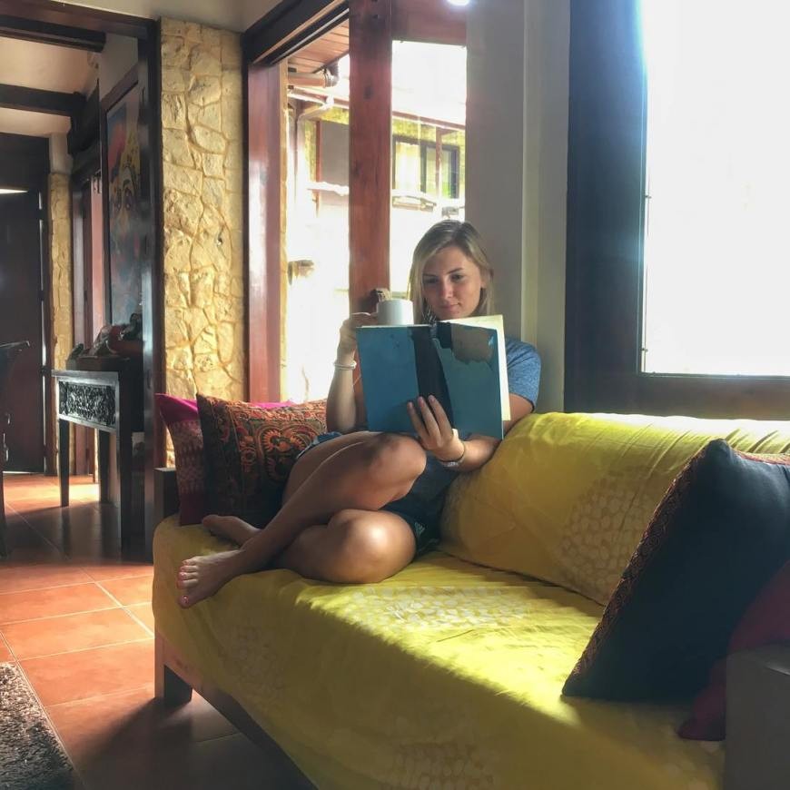 Reading a book while sipping a cup of tea on a yellow couch in the philippines