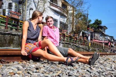 TJ and Alli sitting on the railroad tracks in Shifen