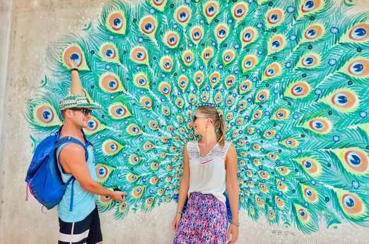 Standing in front of a peacock mural having fun laughing together
