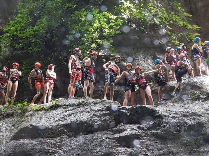 Group of friends standing on a rock cliff while canyoneering in the Philippines