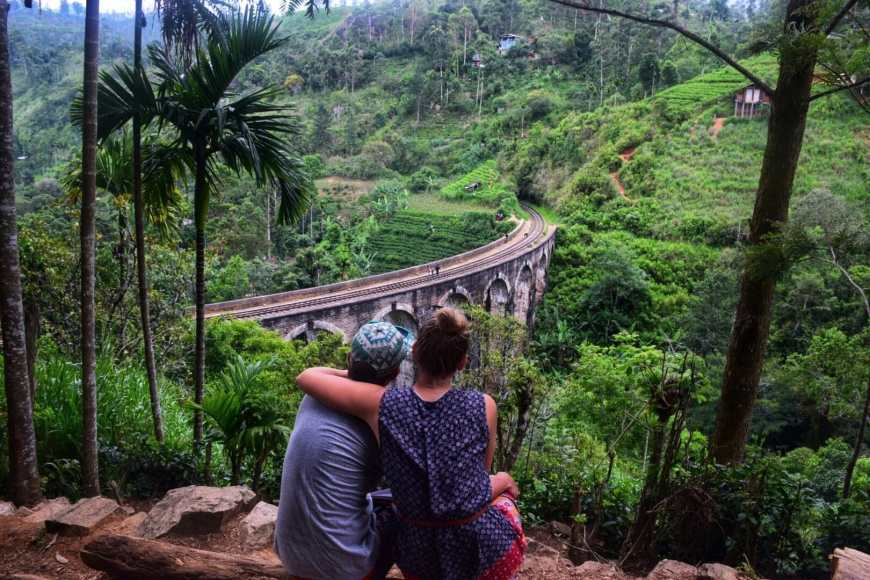 Travel couple sitting above Sri Lanka's famous 9 arch bridge set in lush tea fields in Ella