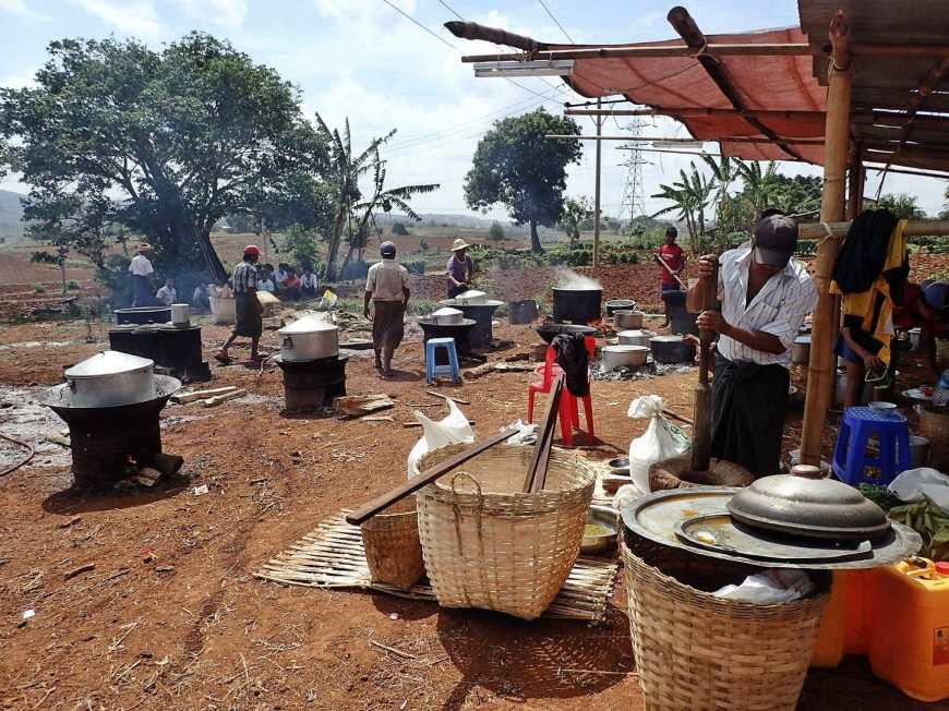 A field filled with different cooking fires covered with pots emanating steam to cook the food for a Burmese wedding