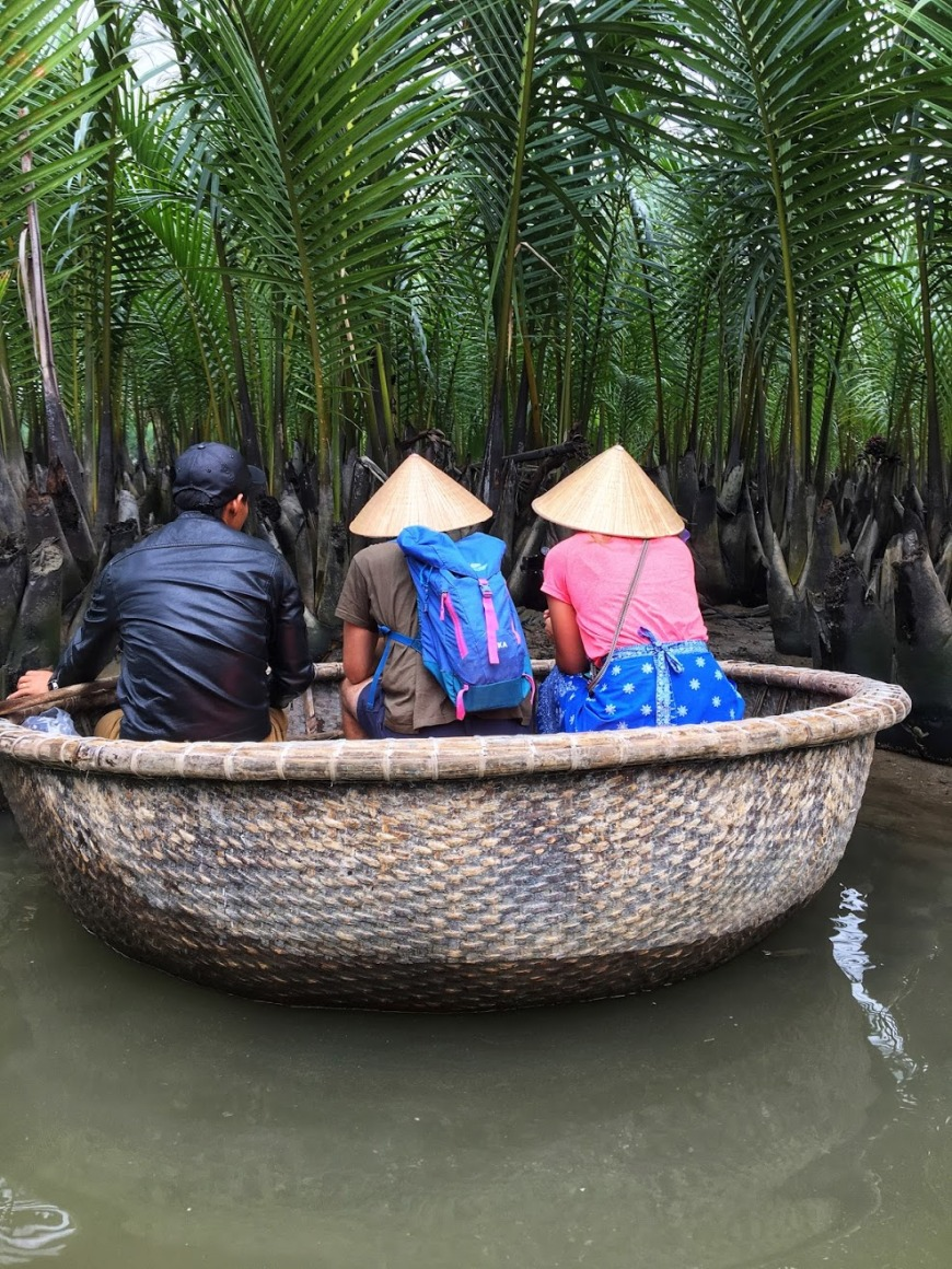Travel Couple in traditional Vietnamese fishing boat searching for crabs amongst palm fronds on the river