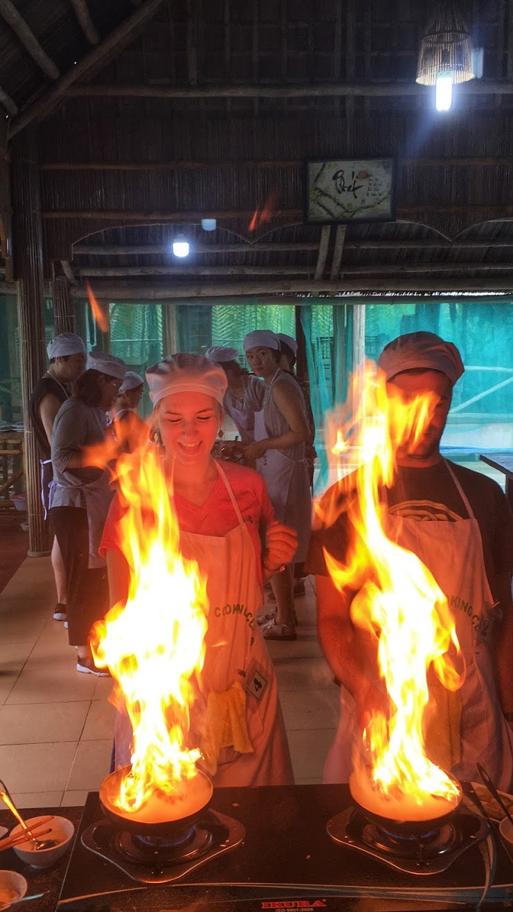 Couple cooking with leaping flames so high they obscure their face at a cooking class in Hanoi, Vietnam