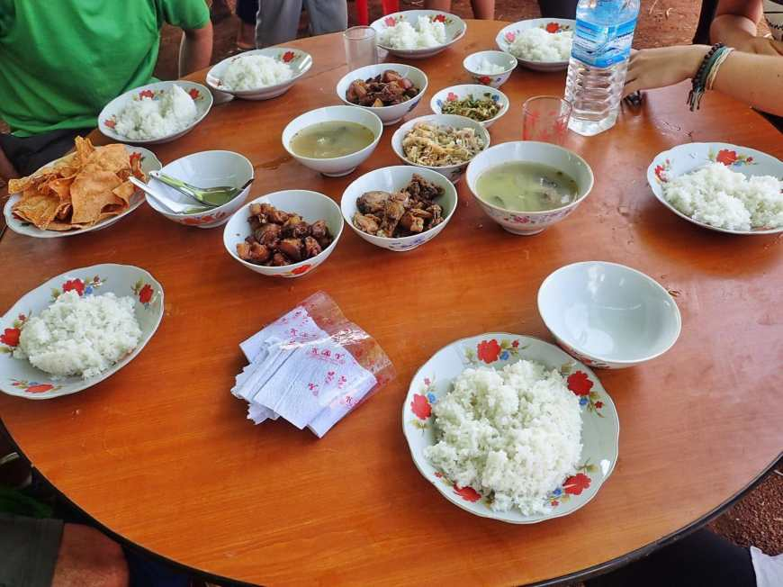 A table full of different Burmese dishes served family style at a Burmese wedding in a village