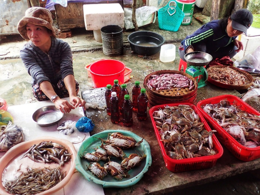 Woman selling crab and other seafood at a local market in Hoi An Vietnam
