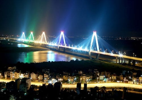 Hanoi's famous Nhat Tan Bridge at night illuminated by colored lights over the water