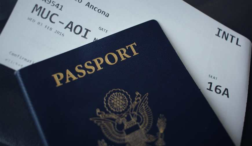 American passport and plane tickets on a black background