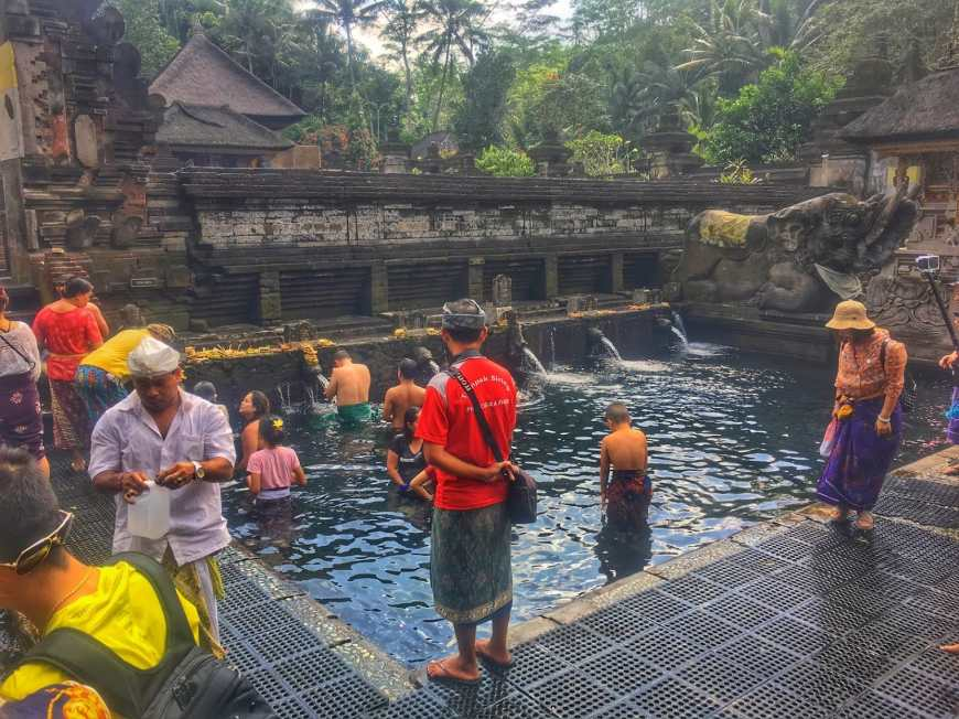 A local guide at TJ & Alli of Life Is Meant For Exploring at Tirta Empul in Bali, Indonesia