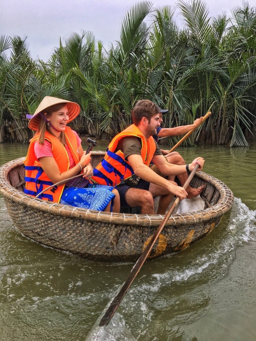 Travel and adventure couple racing a traditional Vietnamese basket fishing boat down a small river before in lifejackets cooking class