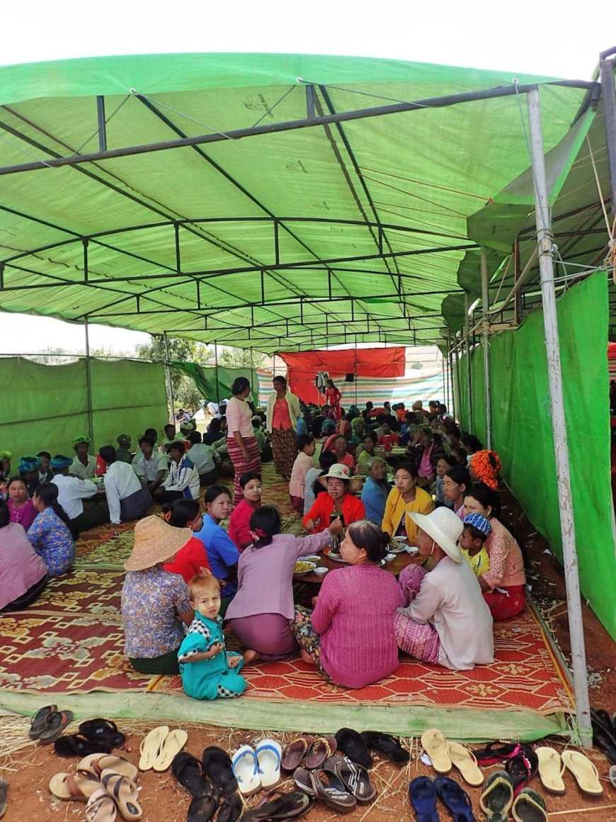 Burmese women sitting on a carpet and enjoying tea and snacks under a green tent at a Burmese wedding in a village in Myanmar