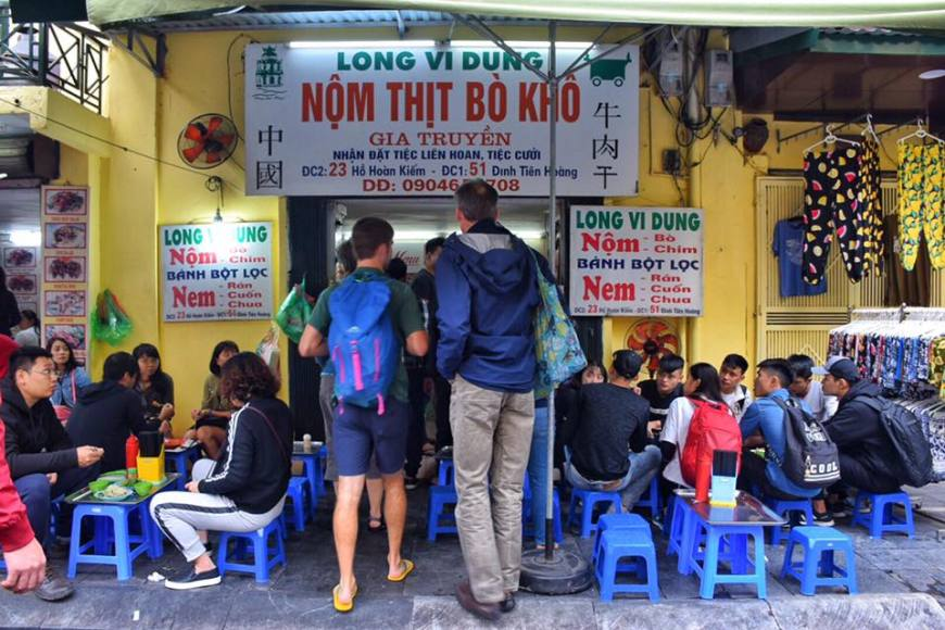 Two westerners walking into a restaurant in Hanoi where all seating is on ankle-high, blue stools